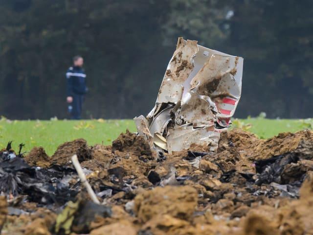 Ein Trümmerteil steckt im Boden, ein Helfer im Hintergrund.