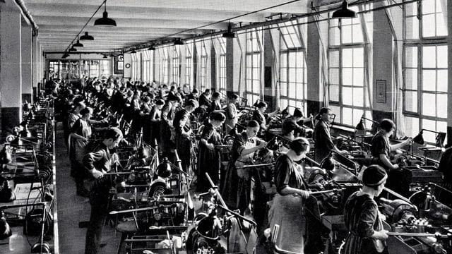 Ein Schwarz-Weiss-Bild: Viele Frauen und Männer arbeiten in einer Revolver-Dreherei.