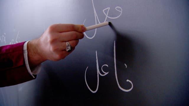 Arabische Schrift auf einer Wandtafel. Eine Hand hält die Kreide.
