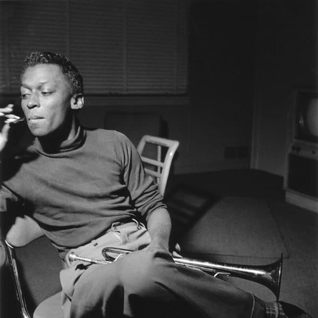 Der junge Miles Davis sitzt auf einem Stuhl. Auf dem Schoss hat er eine Trompete. Er raucht.