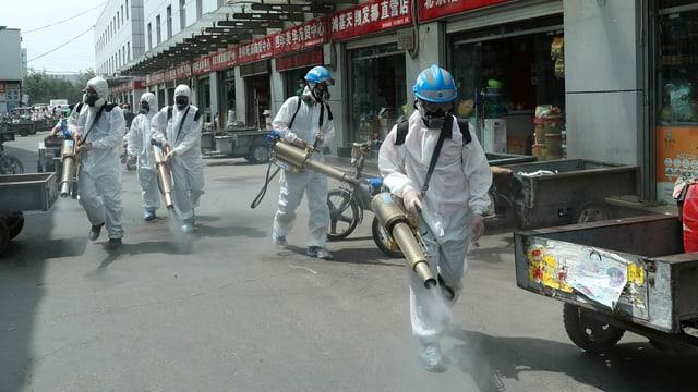 Personen in Schutzanzügen mit Sprühgeräten zur Desinfektion in einer Ladenstrasse.