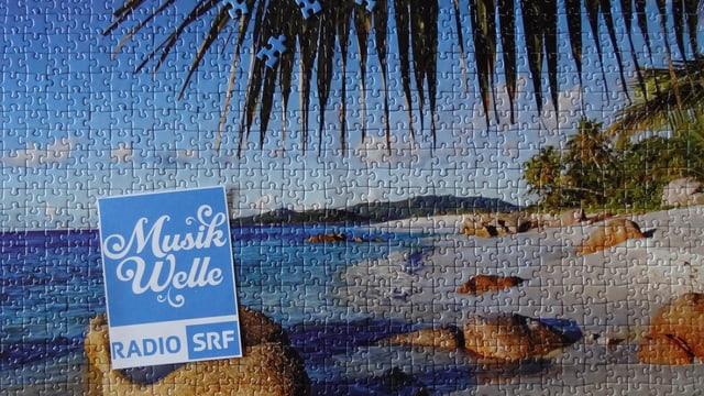 Das Logo von SRF Musikwelle auf einem Puzzle, das einen wunderbaren Blick auf einen Meeresstrand darstellt.