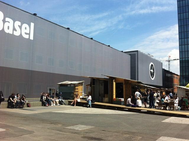 Besucherinnen und Besucher der Art ruhen sich aus im Favela Café.
