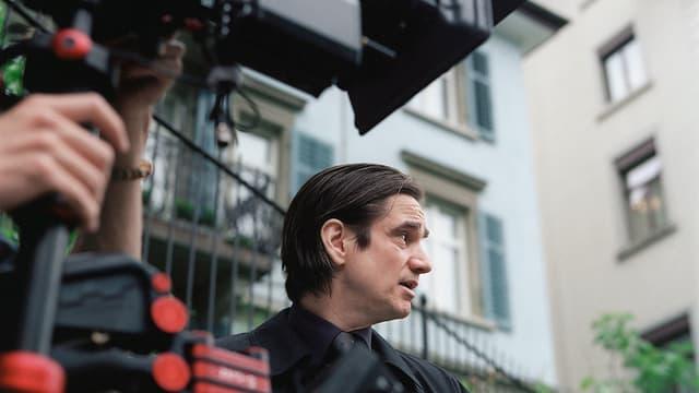Ein Mann mit schwarzen Haaren wird gefilmt.