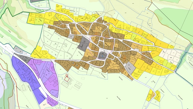 Survista da la fracziun da Ramosch - mellen parcellas da fabrica - brin il center dal vitg e violet la zona da mastergnanza