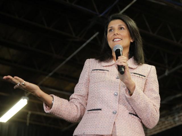 Frau spricht mit Mikrofon in der Hand