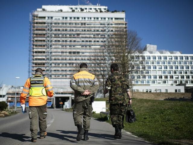 Ein Zivilschützer und ein Angehöriger des Militärs gehen Richtung Spital.