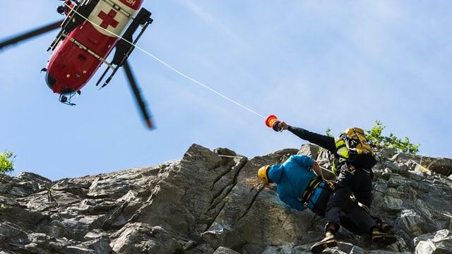 Ein Helikopter, darunter in der Felswand zwei Personen.