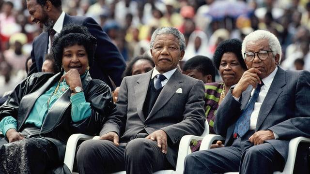 Menschenmenge sitzt wartend auf einer Tribüne. Vorne mittig ist Nelson Mandela zu erkennen.