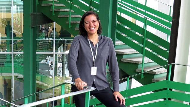 Eine Frau steht an einer grünen Treppe
