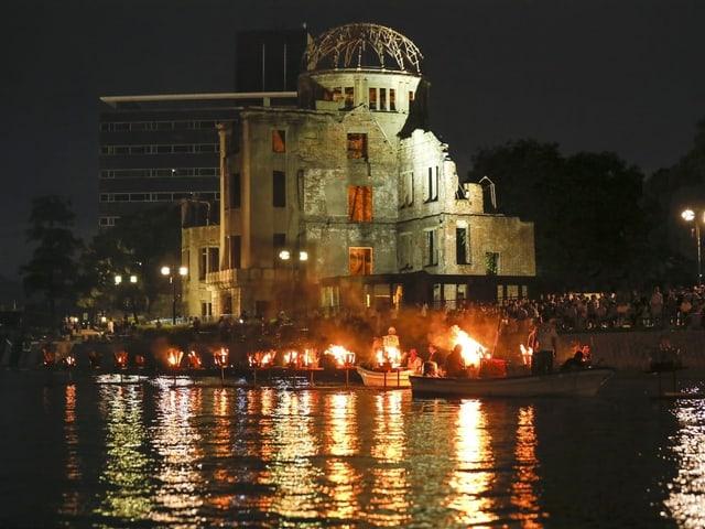Blick auf das ehemalige Regierungsgebäude und Menschen, die mit Feuern in Schiffen den Opfern des Atombombenangriffs gedenken.