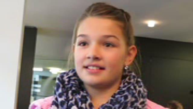 Ein Mädchen in einer rosa Jacke und einem bunten Schal