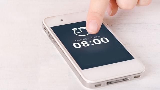 Frau tippt auf den Smartphone-Bildschirm, auf dem ein Weckeralarm zu sehen ist.