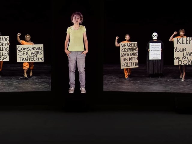 Ein Junge steht zwischen Frauen, die Plakate hochhalten.