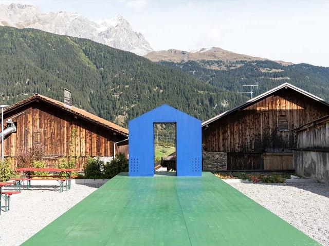Eine blaue Haus-Installation auf grünem Kunstrasen.