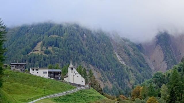 Kirche in bBnn/VS, darüber tiefe Wolken den Berghängen entlang.