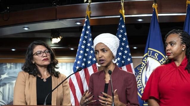 Drei Frauen an Rednerpult. Dahinter US-Fahnen. Eine Frau trägt einen Turban.