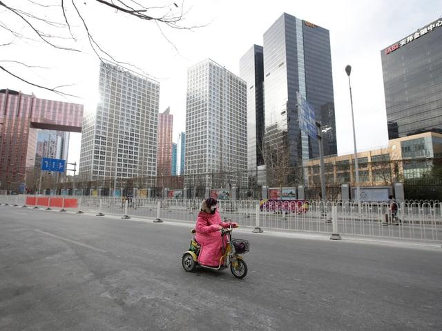 Frau fährt Motorrad in leerer Strasse in Peking
