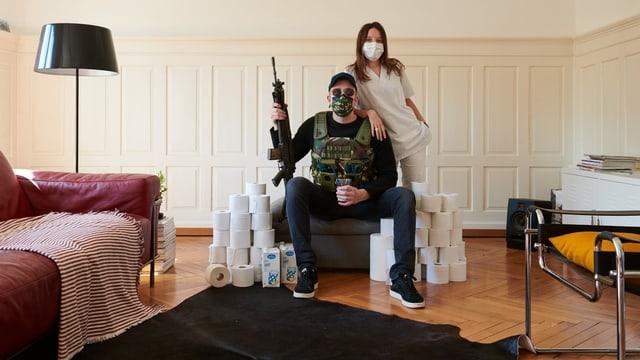 Eine Krankenschwester und ein Mann mit Maske und Sturmgewehr, umgeben von WC-Papier.