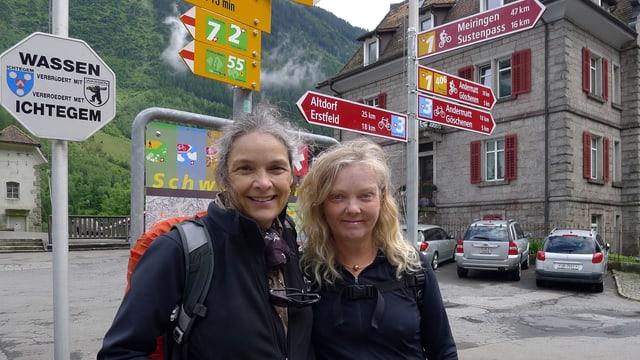Zwei Frauen vor Wanderwegweiser.