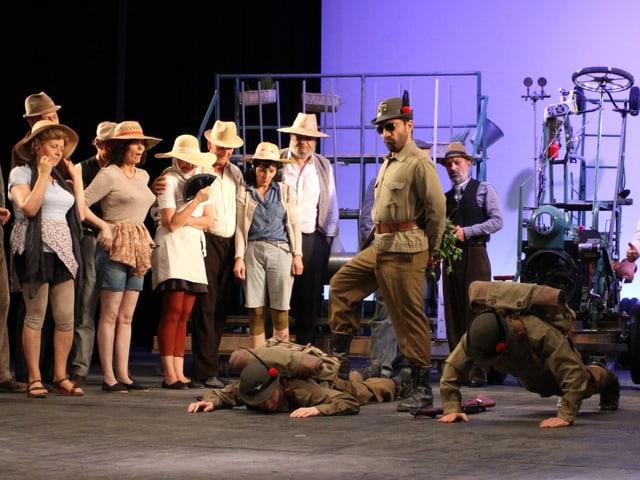 Darsteller Belcore trägt zusammen mit zwei weiteren Personen Soldatenuniform, mehrere Damen schauen der Szenerie zu.