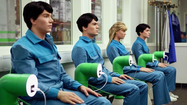 Vier menschenähnliche Roboter sitzen in Ladestationen und werden per Kabel mit Strom versorgt.