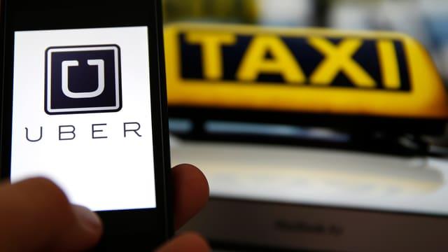 Smartphone mit der Uber App neben einer Taxi-Leuchte
