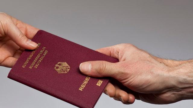 Zwei Hände halten einen deutschen Pass.