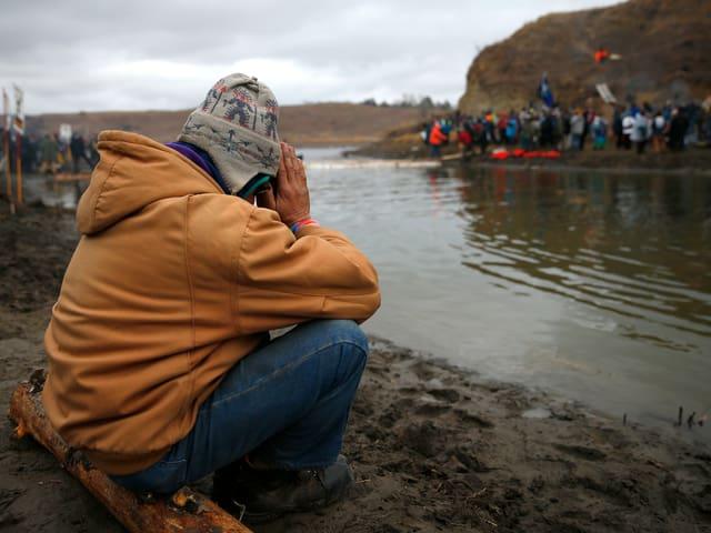 Ein Mann betet an Fluss.