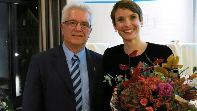 Pierre-Yves Grivel und Claudine Esseiva, mit einem Blumenstrauss, lachen in die Kamera.