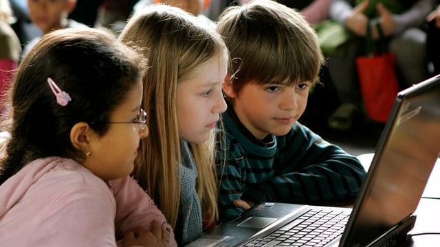 Drei Kinder sitzen vor einem Notebook und schauen aufmerksam auf den Bildschirm.