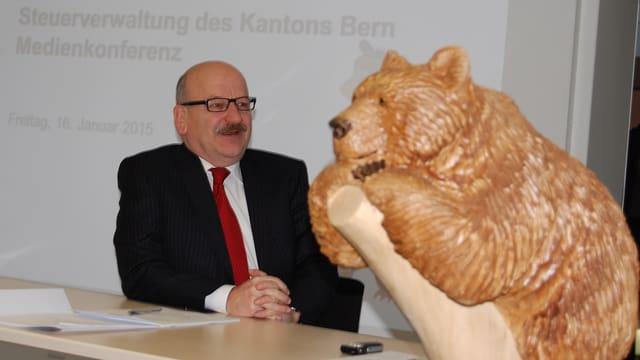 Der bernische Steuerverwalter Bruno Knüsel mit seinem Maskottchen, einem Bären aus Holz