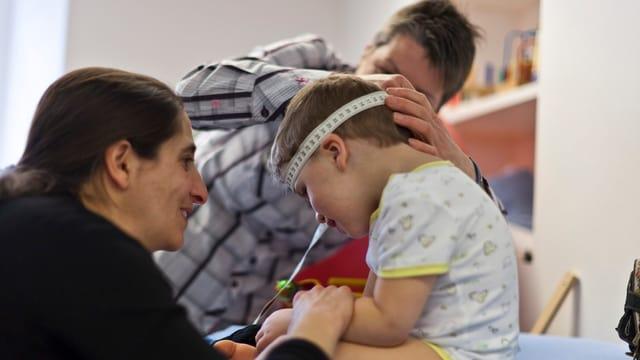 Zwei Frauen kümmern sich um ein Kleinkind.