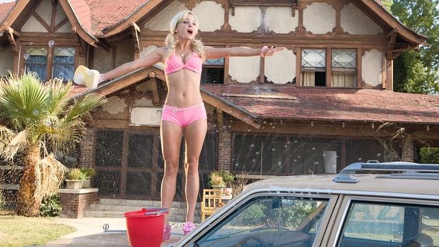 Frau im rosa Bikin steht mit Putzschwamm auf einer Autohaube