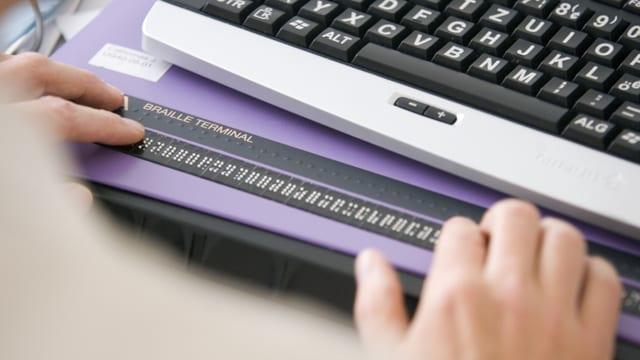 Ein Mann sitzt vor einem Computer an einer Tastatur für die Blindenschrift.