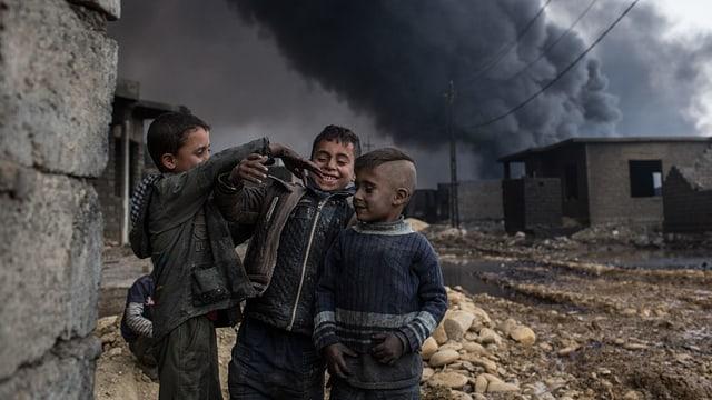 Drei Jungen, alle schwarz vor Russ, vor ausgebrannten Häusern.