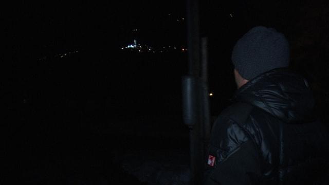 Ein Mann mit dunkler Daunenjacke läuft zum Dorf Surrein, wo nur einzelne Fenster beleuchtet sind.