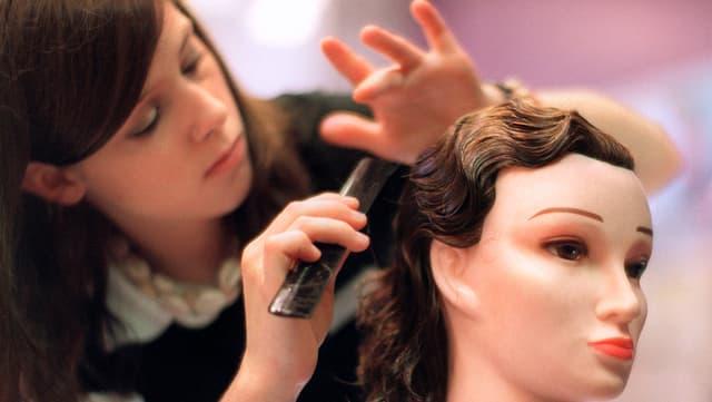 Ein Coiffeur-Lehrling frisiert einen Puppenkopf