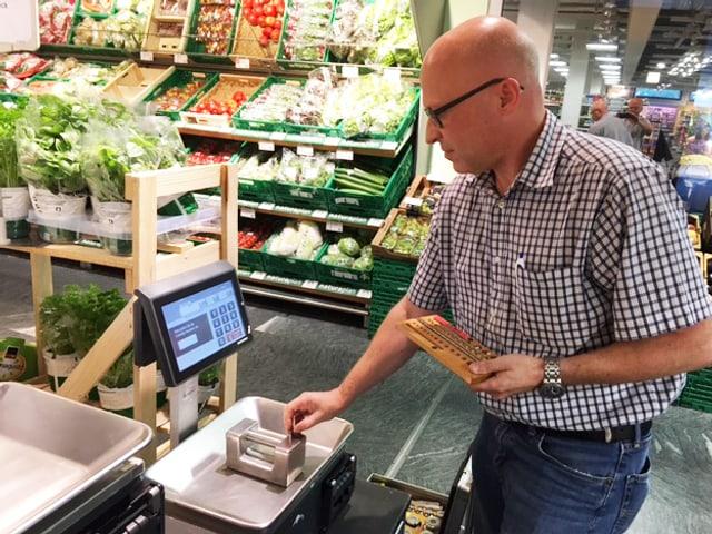 Eichmeister legt verschiedene Gewichte auf eine Gemüsewaage.