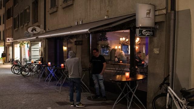 Bar an einer gepflasterten Altstadtgasse. Draussen ist es dunkel, zwei Männer stehen vor der BAr. Durch das Fenster sieht man Menschen im beleuchteten Innenraum.