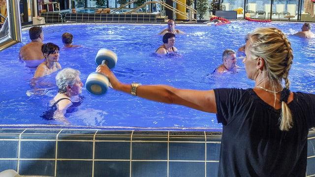Senioren planschen in einem Wasserbecken, während eine Sportinsktruktorin am Bassinrand eine Hantel waagrecht in die Luft hält.