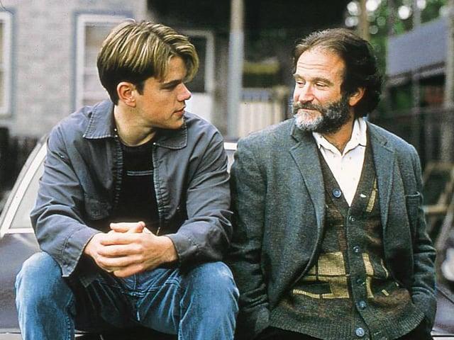 Matt Damon und Robin Williams sitzen nebeneinander und schauen sich an.