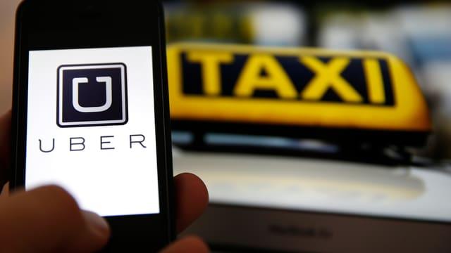 Eine Hand hält ein Smartphone mit der Uber-App vor einem Taxi.