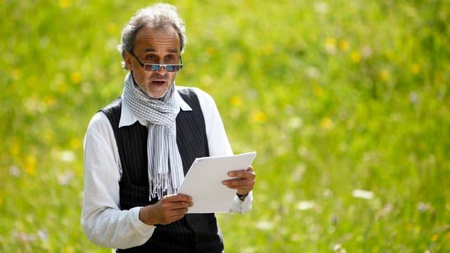 Daniel Schwartz steht auf einer Wiese, hält ein Blatt Papier in der Hand.
