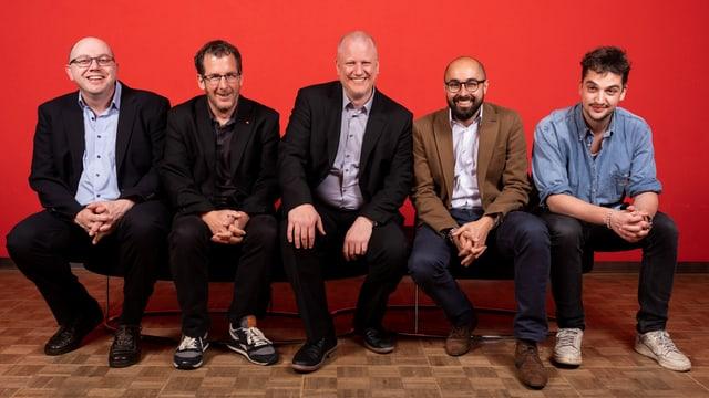 5 Männer vor rotem Hitergrund.