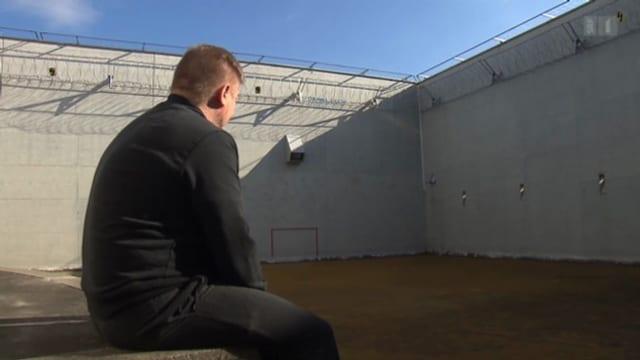 Ein Untersuchungshäftling sitzt auf einer Bank im Innenhof eines Gefängnisses.