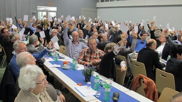 Saal mit Leuten, die Hände in die Höhe halten