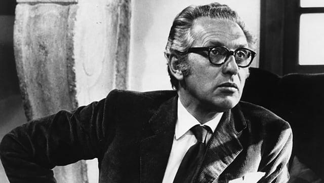 Schwarzweissfoto eines Mannes in Brille und Anzug mit ernstem Gesicht.