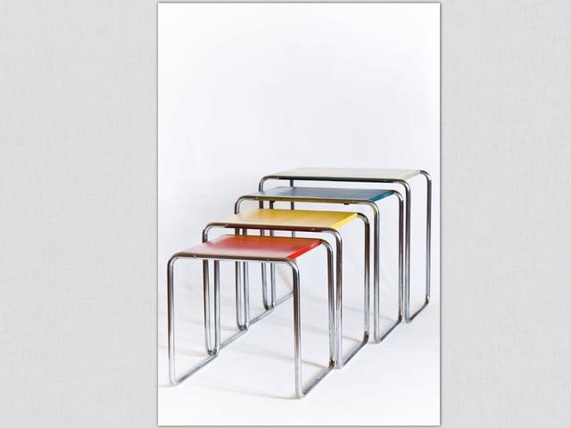 Kleine, bunte, untereinanderschiebbare Tischchen.