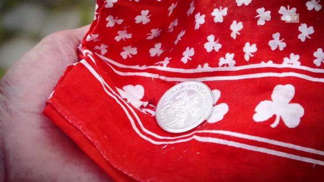 Ein silberner Taler auf einem ro-weissen Tuch.